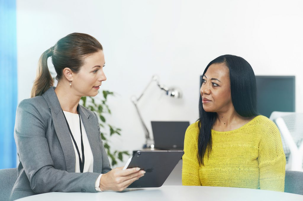 A health professional holding a clipboard talking with a patient